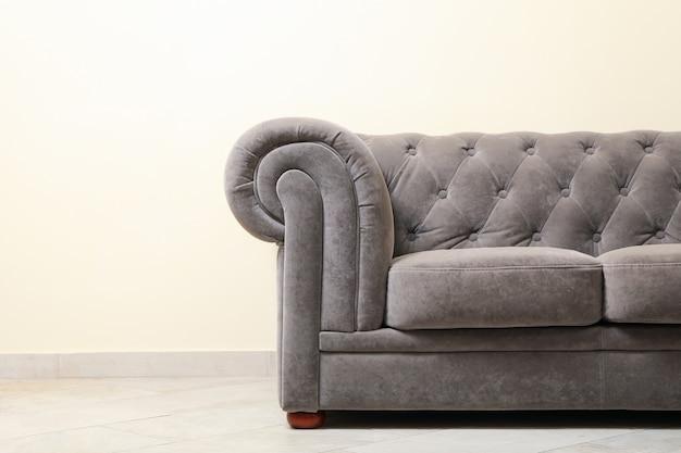 Proste wnętrze z sofą na tle jasnobeżowej ściany