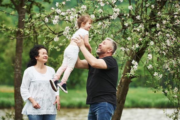 Prosto w powietrze. wesoła para spędza miły weekend na świeżym powietrzu z wnuczką. dobra wiosenna pogoda