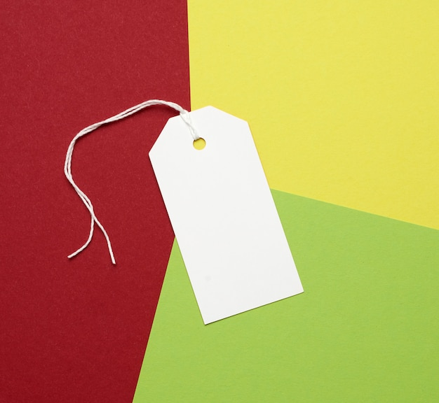 Prostokątna metka z białego papieru na linie na kolorowej przestrzeni, leżała płasko