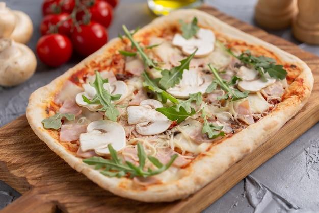 Prostokątna pizza z pieczarkami, pomidorami i rukolą na drewnianej desce do krojenia