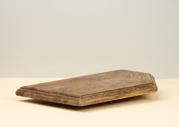 Prostokątna pusta brązowa drewniana deska kuchenna na żółtym tle, naczynia