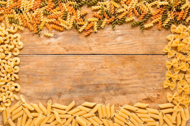 Prostokątna rama wykonana z różnych rodzajów surowego makaronu na drewnianym stole