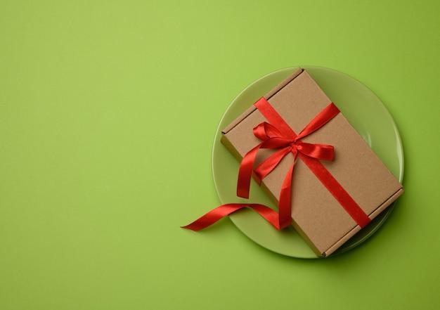 Prostokątne brązowe pudełko kartonowe przewiązane czerwoną wstążką i leżące na zielonej ceramicznej powierzchni, widok z góry, kopia