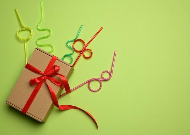 Prostokątne brązowe pudełko kartonowe przewiązane czerwoną wstążką i leży na zielonym tle, widok z góry.