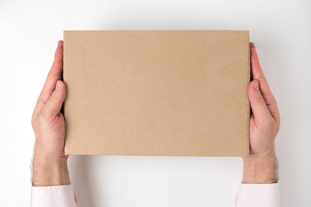 Prostokątne kartonowe pudełko w męskie ręce. koncepcja usługi dostawy. widok z góry
