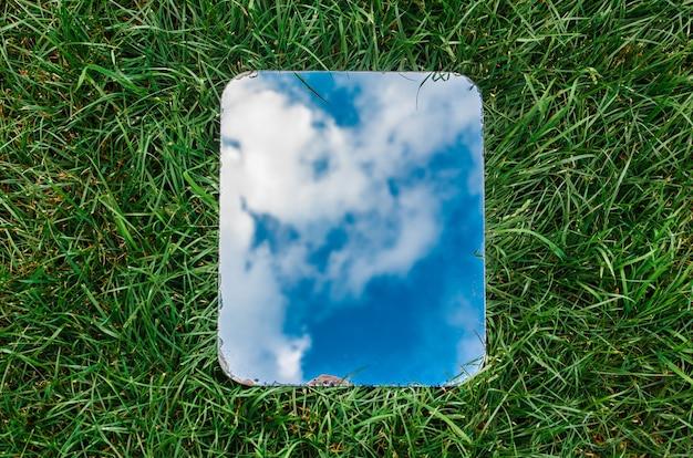 Prostokątne lustro odbijające błękitne niebo z chmurami leżącymi na zielonej trawie.