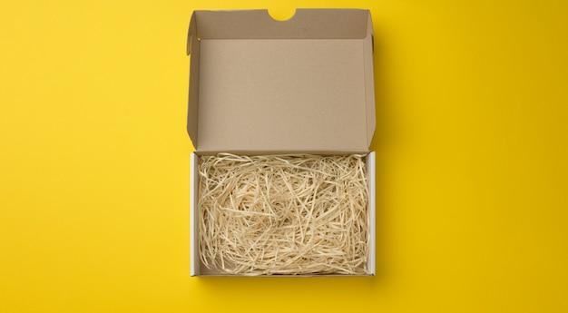 Prostokątne otwarte pudełko z tektury falistej z trocinami w środku. opakowania, pojemniki do transportu na żółtym tle