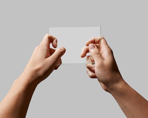 Prostokątne przezroczyste szkło w męskich rękach na szarym tle dla tekstu