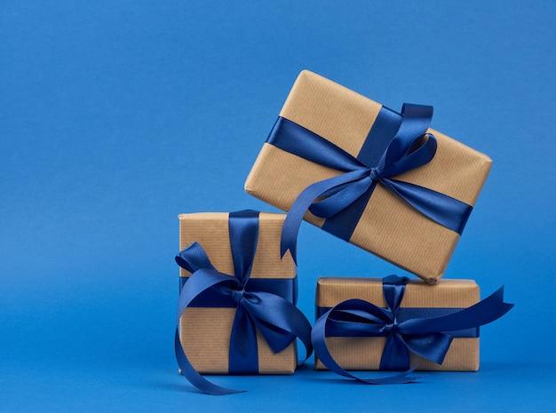 Prostokątne pudełko owinięte w brązowy papier pakowy i przewiązane jedwabną niebieską wstążką