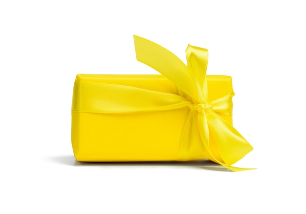 Prostokątne pudełko z prezentem zawinięte w żółty papier i przewiązane jedwabną żółtą wstążką, tło białe