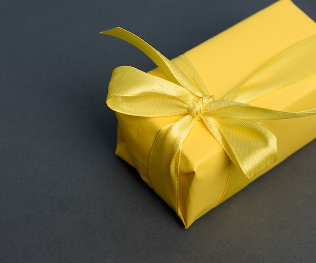 Prostokątne pudełko z prezentem zawinięte w żółty papier i przewiązane jedwabną żółtą wstążką, widok z góry, czarne tło