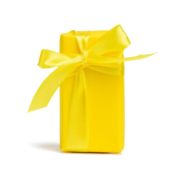 Prostokątne pudełko z prezentem zawinięte w żółty papier i przewiązane jedwabną żółtą wstążką