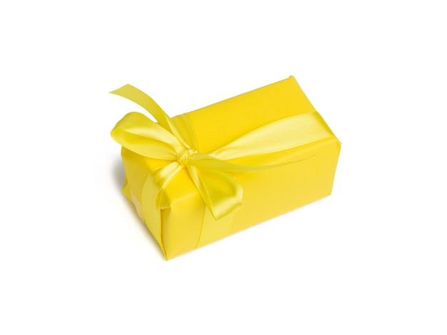 Prostokątne pudełko z prezentem zawinięte w żółty papier i przewiązane żółtą jedwabną wstążką, tło białe