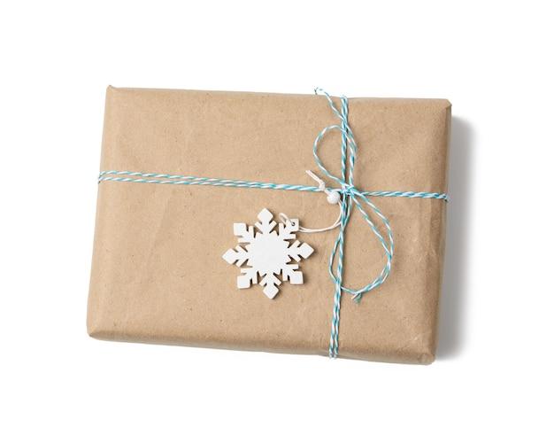 Prostokątne pudełko zawinięte w brązowy papier pakowy i przywiązane liną, prezent na białym tle
