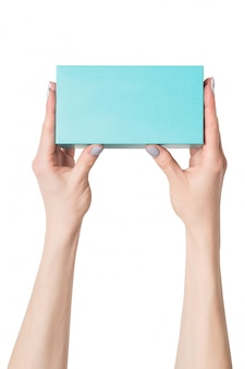 Prostokątne turkusowe pudełko w rękach kobiet.