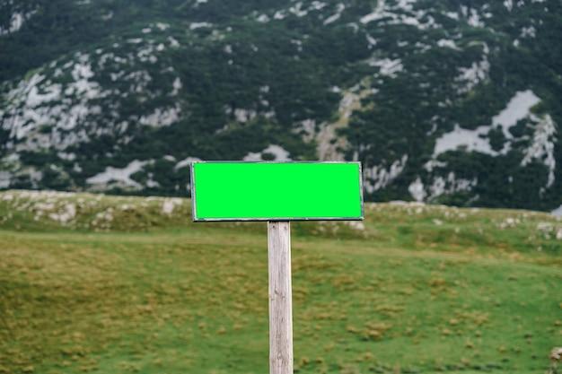 Prostokątny pusty znak na drodze z ośnieżonymi górami na powierzchni