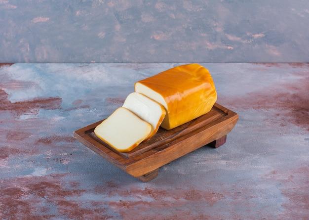 Prostokątny ser w plasterkach na desce na marmurowej powierzchni