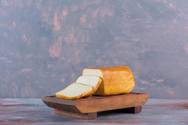 Prostokątny ser w plasterkach na desce, na tle marmuru.