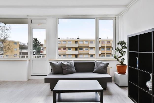 Prosty czarny stolik kawowy i półki z szarą kanapą w salonie z drzewkiem bonsai na tle domu mieszkalnego z widokiem na okno