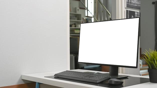 Prosty obszar roboczy z komputerem i rośliną domową na białym stole.