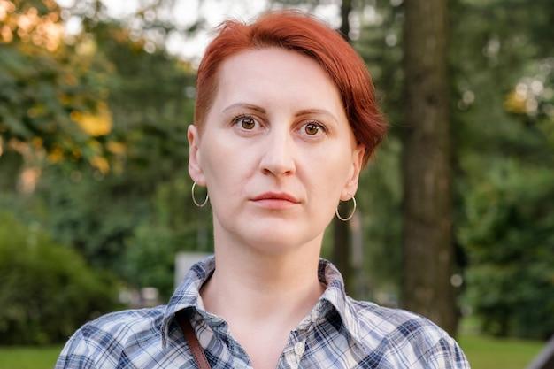 Prosty portret młodej kobiety z krótkimi włosami kobiety w kraciastej koszuli na tle drzew