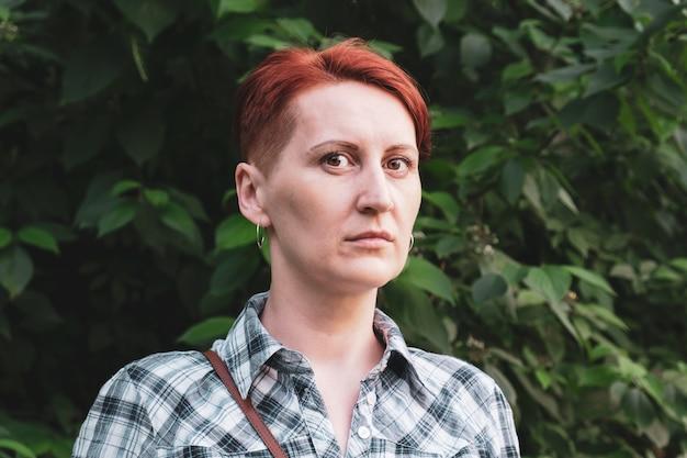 Prosty portret rudowłosej młodej kobiety z krótkimi włosami