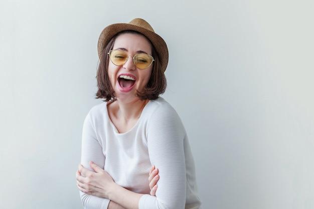 Prosty pracowniany portret modniś mody uśmiechnięta dziewczyna w modnych żółtych okularach przeciwsłonecznych i kapeluszu odizolowywających na bielu