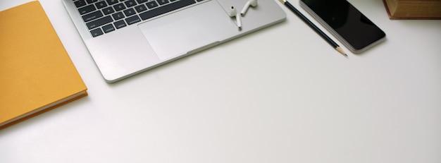 Prosty stół roboczy z urządzeniem cyfrowym, papeterią i miejscem do kopiowania na białym biurku