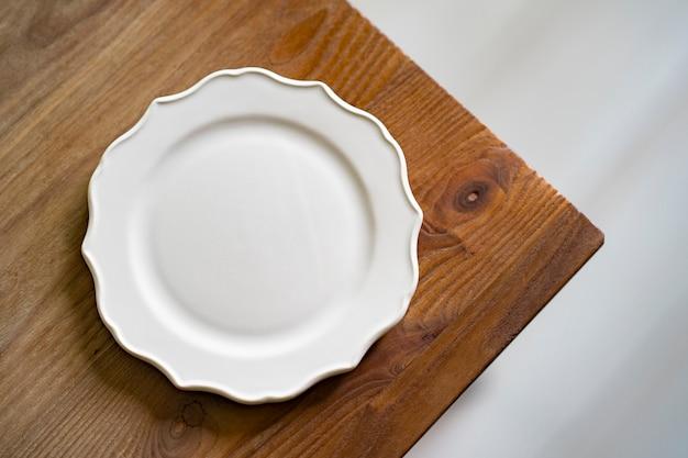 Prosty talerz ceramiczny umieszczony na drewnianym stole w jadalni