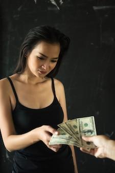 Prostytutka biorąc banknotów dolarowych. zapłać za seks