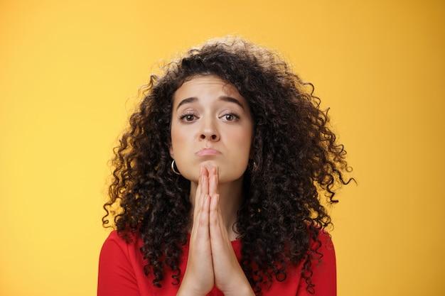 Proszę, błagam, portret smutnej i uroczej dziewczyny z kręconymi włosami o wydętych anielskimi oczami, trzymając się za ręce w ...