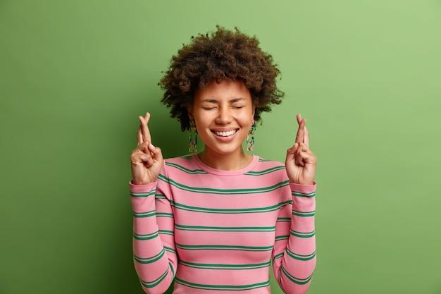 Proszę, chcę to. wesoła młoda afroamerykańska kobieta uśmiecha się szeroko ubrana w swobodny sweter w paski z krzyżem palców sprawia, że marzenie błaga boga o spełnienie marzeń izolowanych na jaskrawozielonej ścianie