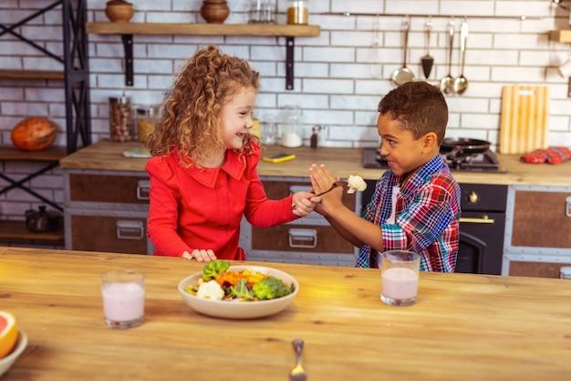 Proszę nie. pozytywnie zachwycony międzynarodowy chłopiec stojący w pół pozycji, nie chcący jeść warzyw