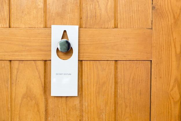 Proszę nie przeszkadzać znak na zamknięte drewniane drzwi pokoju hotelowego