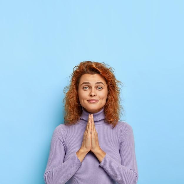 Proszę, pomóż mi jeszcze raz! przyjaźnie wyglądająca ruda kobieta trzyma dłonie razem, prosi o coś, ma nadzieję, że będzie lepiej, nosi fioletowy swobodny sweter, przyjemnie się uśmiecha, kopiuje miejsce w górę