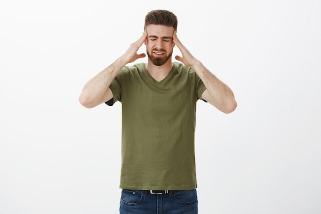 Proszę, przestań mi dmuchać w głowę. portret niespokojnego przystojnego brodatego mężczyzny dotykającego głowy i skroni zamykających oczy od bolesnego uczucia migreny, nienawiści kłócącej się niezadowolonej z głośnego krzyku jako kaca