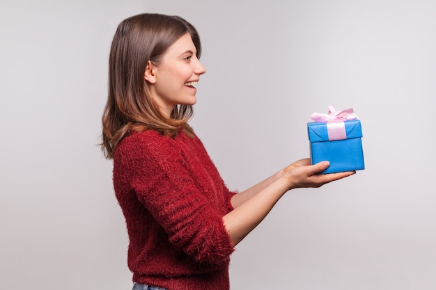 Proszę, weź ten świąteczny prezent! widok z boku, szczęśliwa dziewczyna dająca ozdobne pudełko i powitanie