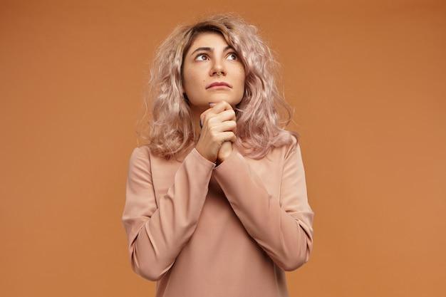 Proszę wybacz mi. piękna modna młoda kobieta z kolczykiem w nosie i różowawymi włosami trzymająca się za ręce i patrząc w górę, modląc się, błagając, błagając o przebaczenie