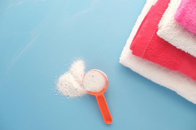 Proszek do prania w plastikowej łyżce na niebieskiej powierzchni