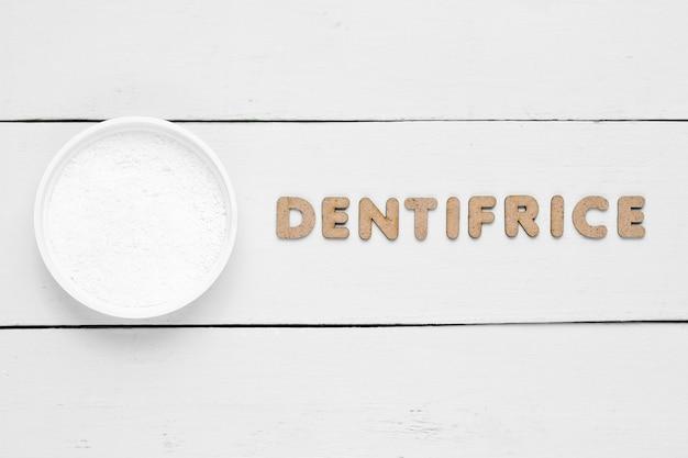 Proszek do zębów na białym tle ze słowem środek do czyszczenia zębów
