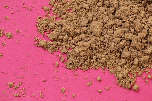 Proszek guarany na różowym tle. super jedzenie. naturalnie energetyczny.
