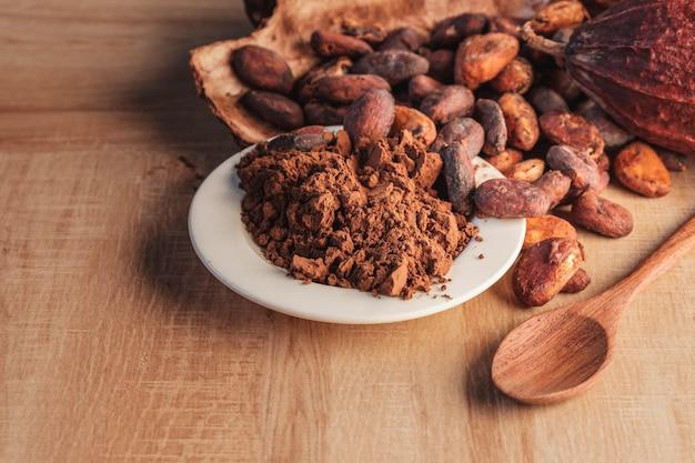 Proszek kakaowy i ziarna kakaowe w strąkach kakaowych na drewnianym stole.