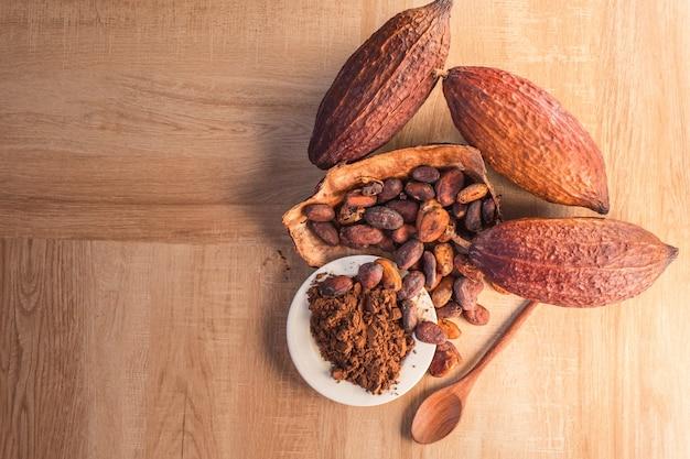 Proszek kakaowy i ziarna kakaowe w strąkach kakaowych na drewnianym tle.