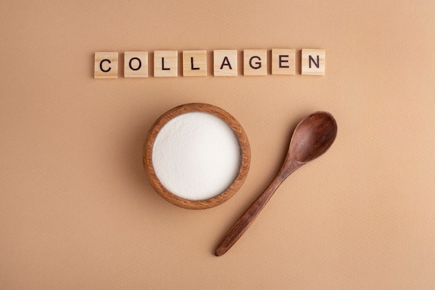 Proszek kolagenowy w drewnianej misce, łyżka, przestrzeń brzoskwiniowa, widok z góry, napis