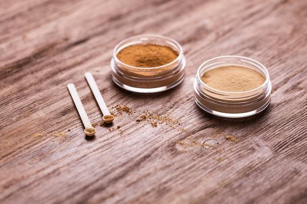 Proszek mineralny w różnych kolorach z dozownikiem łyżkowym do makijażu na drewnianym tle