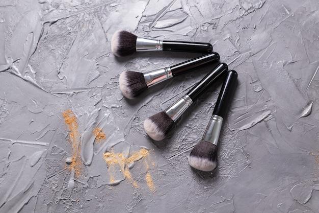 Proszek mineralny w różnych kolorach z pędzlami do makijażu na drewnianym tle widok z góry