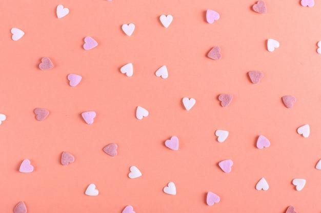 Proszek w kształcie serca, jak cukierki, jest rozrzucony na stole kartkę z życzeniami wesołych świąt.