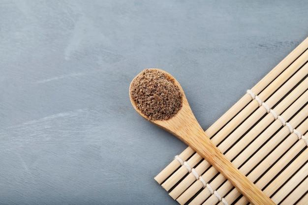 Proszek z ostropestu plamistego lub ekstrakt z ostropestu plamistego w drewnianej łyżce