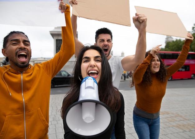 Protestujący ludzie ze średnimi strzałami