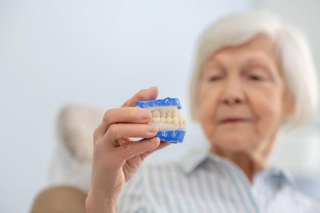 Proteza. starsza kobieta trzyma protezę i wygląda na zamyśloną